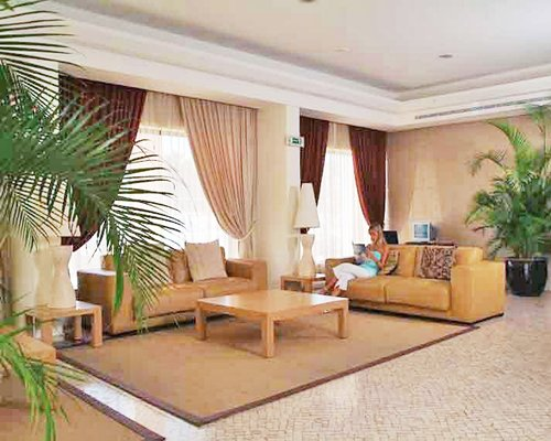 A well furnished indoor lounge area with potted plants.