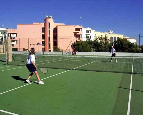 View of ladies playing tennis in an outdoor court alongside the resort.