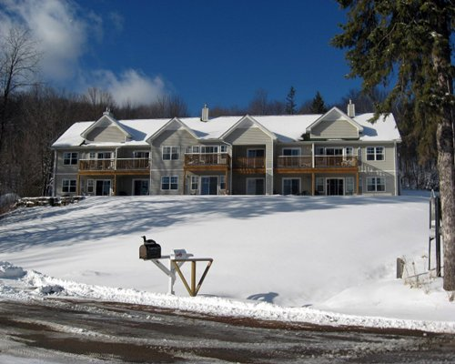 An exterior view of multi story resort unit covered in snow.