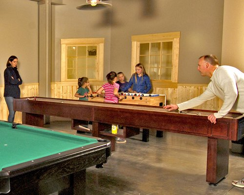 An indoor recreation room with pool table and table soccer.