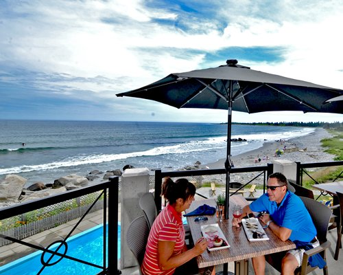 Couple at an outdoor dining area with sunshade and beach view.