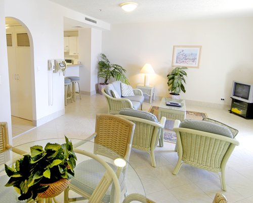 A well furnished living room with television open plan kitchen and dining area.