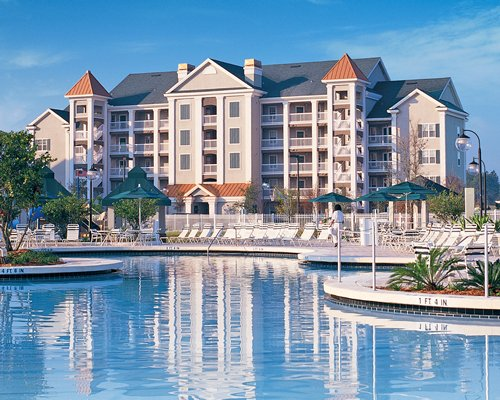 A large outdoor swimming pool with chaise lounge chairs alongside multi story resort units.