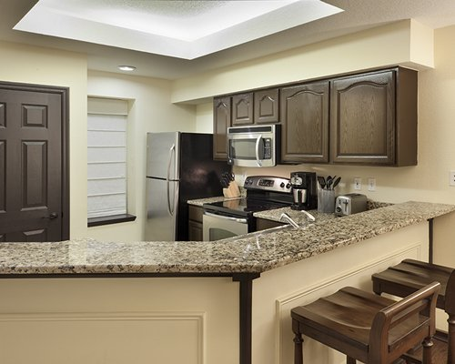 A well equipped kitchen with breakfast bar and microwave oven.