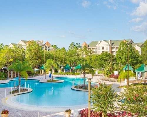 An outdoor swimming pool alongside multi story resort units surrounded by trees.
