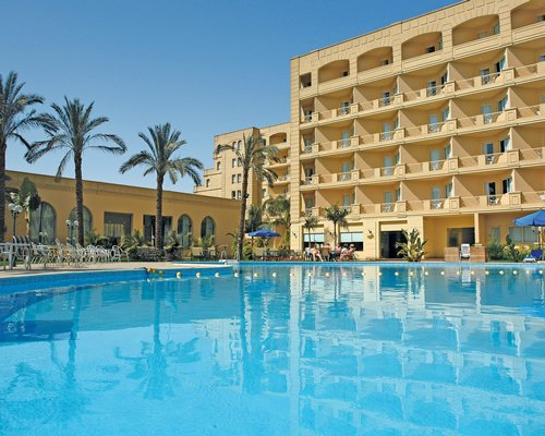 Exterior view of El Wadi Plaza Hotel with large outdoor swimming pool chaise lounge chairs and palm trees.