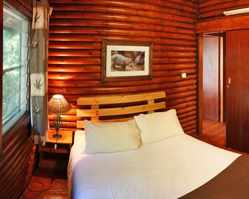 A wooden themed bedroom with a double bed and an outside view.