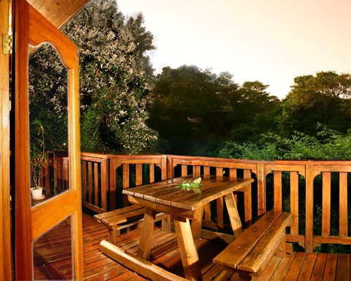 Balcony with picnic table surrounded by wooded area.