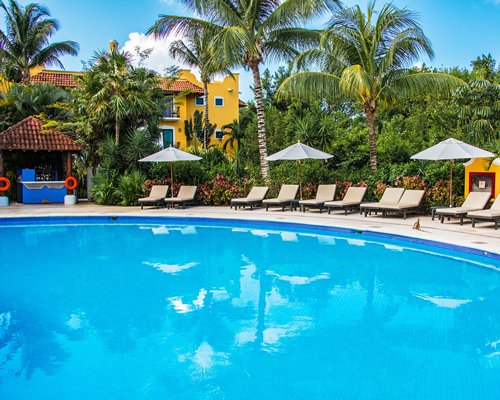 An outdoor swimming pool with chaise lounge chairs umbrellas bar and resort view.