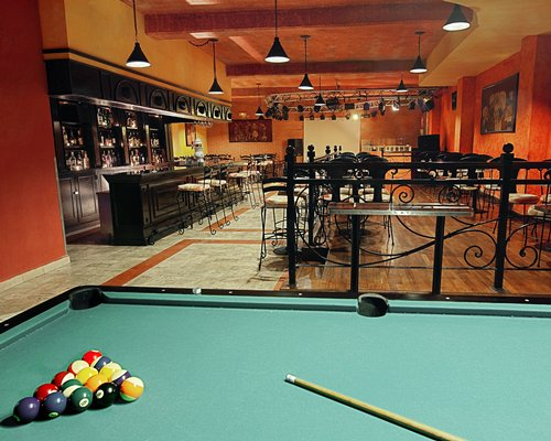 A resort bar with tables and pool table in foreground.