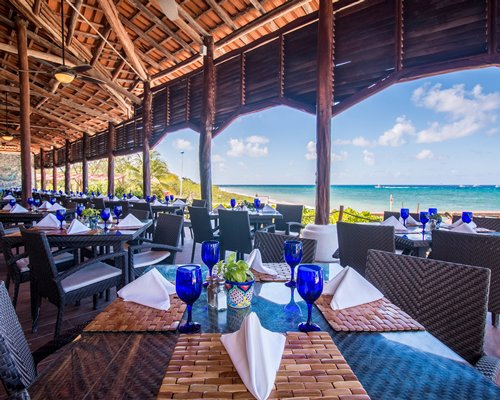 An open-air restaurant with multiple dining tables and ocean view.