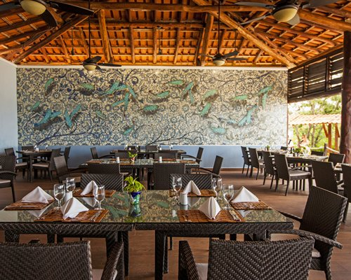 An open air restaurant with tables wall mural and high wooden ceiling.