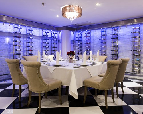 A restaurant interior with large table with wall wine racks.