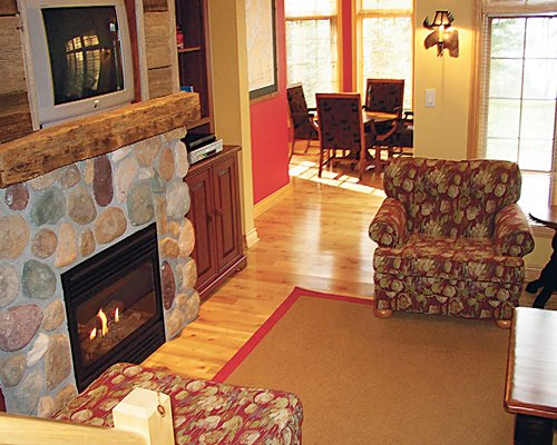 A well furnished living room with fire in the fireplace television dining area and outside view.