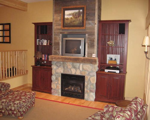 A well furnished living room with fireplace and television.