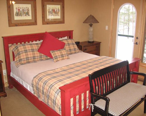 A well furnished bedroom with a queen bed and outdoor view.