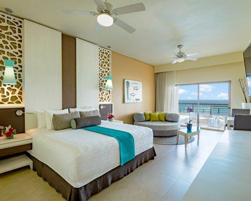 A well furnished living room with king bed television balcony and sea view.