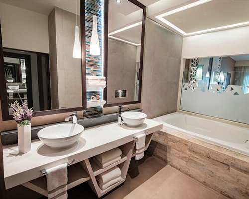 A bathroom with double sink vanity and bath tub.