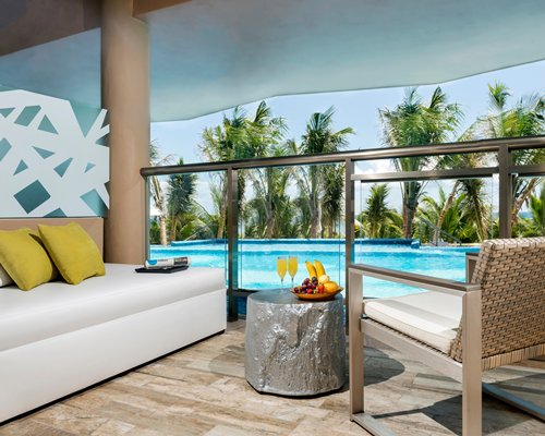 Outdoor lounge area alongside the outdoor swimming pool with palm trees.