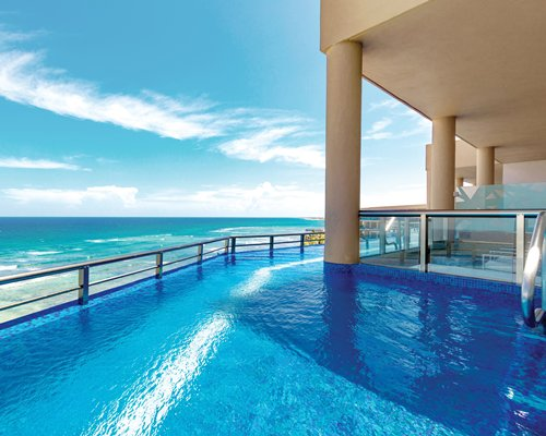 An outdoor swimming pool alongside the ocean.