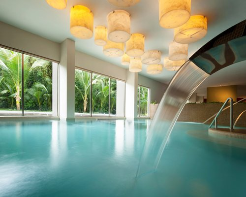 An indoor swimming pool with water feature and an outside view.