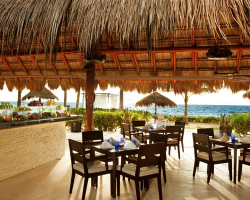Outdoor restaurant covered with a thatched roof alongside the ocean.