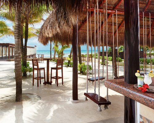 Outdoor thatched covered bar with swing alongside the ocean.