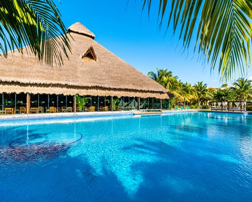 Outdoor swimming pool with beach beds and palm trees alongside thatched covered restaurant.
