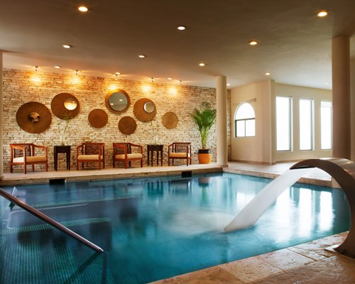 An indoor swimming pool with a water feature and patio furniture.