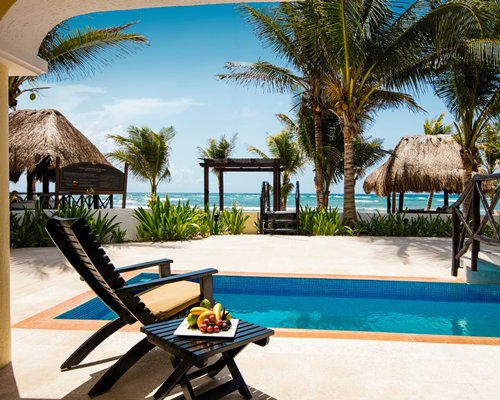 Outdoor swimming pool with patio furniture and thatched sunshades alongside the beach.