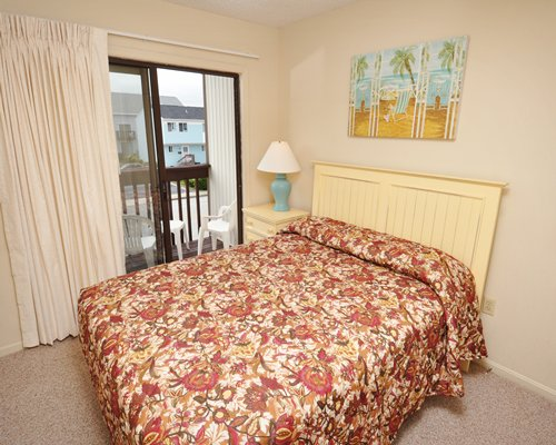 A well furnished bedroom with a queen bed and patio.