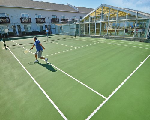 An outdoor tennis court alongside multi story unit with private balconies.