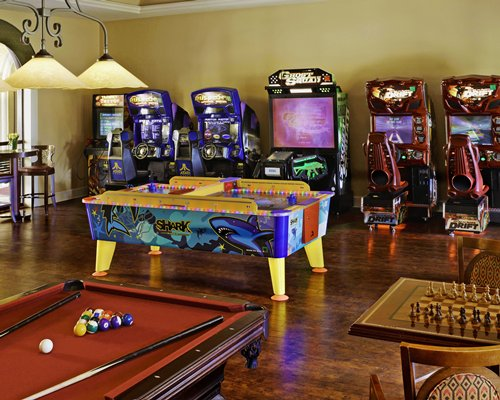 A recreational room with pool tables arcade game and chess.
