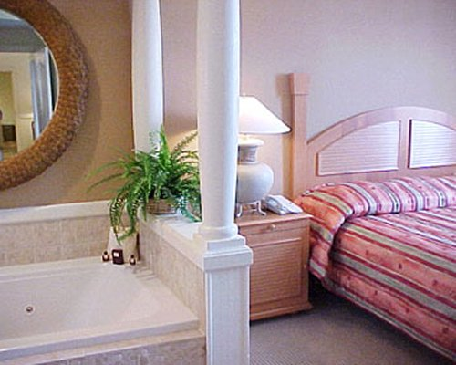 A well furnished bedroom with a bathtub and vanity.