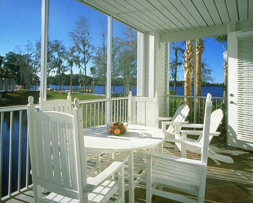 A balcony with patio furniture and a view of the lake.
