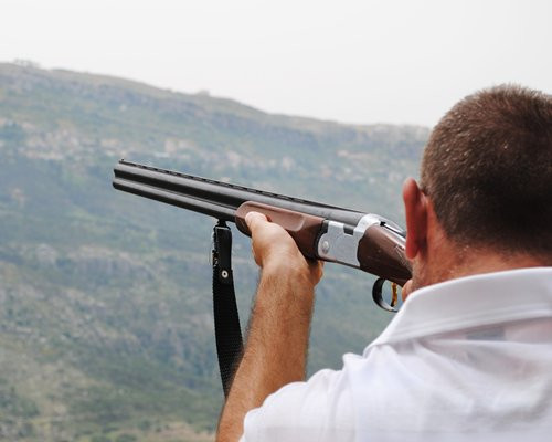 A person shooting alongside mountains.