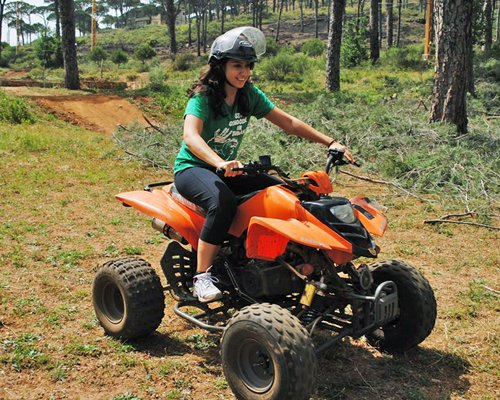 Girl riding a go kart at wooded area.
