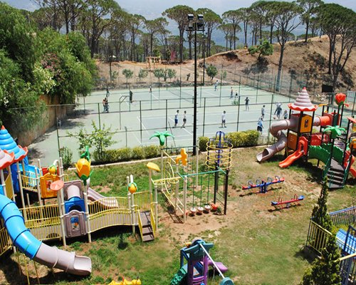 Outdoor kids recreation area with playscape alongside tennis court.