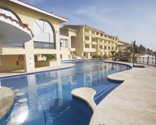 A large outdoor swimming pool alongside multi story resort units.