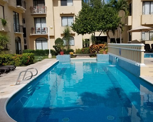 View of All Ritmo Cancun Resort with water park and thatched covered bar.