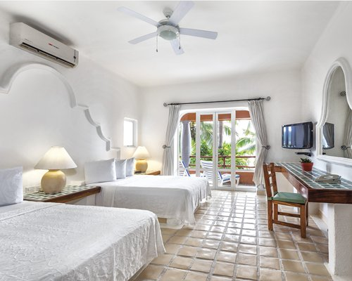 A well furnished bedroom with a double king bed and television alongside the balcony.