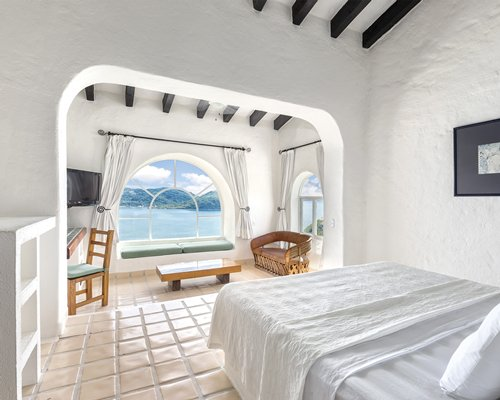 A well furnished bedroom with a king bed and the beach view.