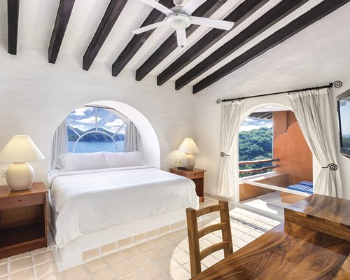 A well furnished bedroom with a king bed and outside view.