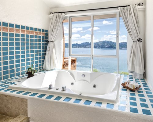 A bathroom with a bathtub with ocean view.