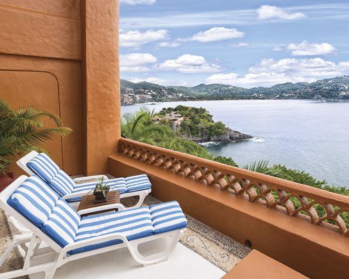 Balcony with chaise lounge chairs and view of the ocean.