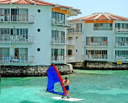 A man windsurfing alongside the multi story resort units.