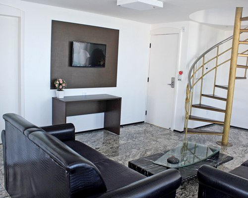 A well furnished living room with a pull out sofa television and a spiral staircase.