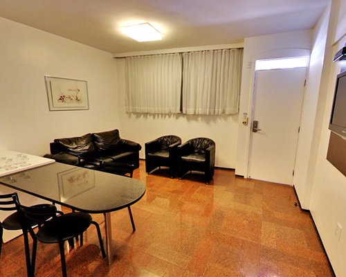 A well furnished living room with television and breakfast bar.