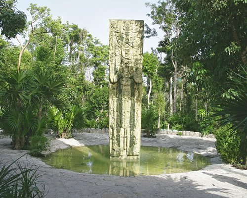 A view of stone statue pillar surrounded by woods.