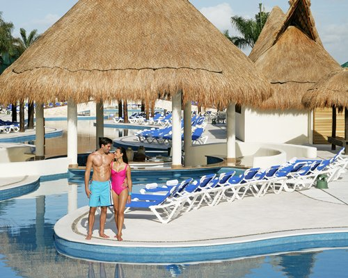 A couple standing near the outdoor swimming pool with chaise lounge chairs and thatched sunshades.